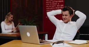 Ståenden av en ung lyckad affärsman ser lycklig, når det har avslutat hans arbete på bärbara datorn långsam rörelse Begrepp: nytt arkivfilmer