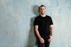 Ståenden av en ung man i en svart T-tröja lutade mot en tappninggrå färgvägg kopiera avstånd fotografering för bildbyråer