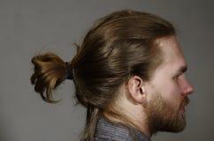 Ståenden av en ung man med ett skägg och mustaschen sid över mörker Arkivfoton