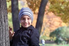 Ståenden av en ung pojke med ett leende på hans framsida nära ett träd i parkerar i höst arkivbild