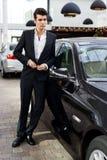 Den unga stiliga manen, modellerar av danar, med lyxiga bilar Royaltyfria Bilder