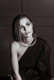 Ståenden av en ursnygg flicka i studion i en mans omslag, en halsband med kort vått hår ser inte kameran i BW Fotografering för Bildbyråer