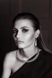 Ståenden av en ursnygg flicka i studion i en mans omslag, en halsband med slicked-baksida hår ser kameran i BW Royaltyfria Bilder