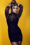 Ståenden av en ursnygg ung glam dam med updofrisyren som bär åtstramande kort svart, snör åt klänningen och strumpor Royaltyfria Bilder