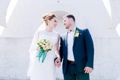Ståenden av ett älskvärt par firade smekmånad på en bröllopdag med en bukett i hand mot bakgrunden av en ortodox Royaltyfri Foto