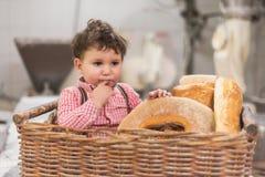 Ståenden av ett gulligt behandla som ett barn inom en korg med bröd i bagerit royaltyfri foto