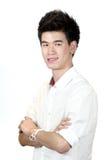 Ståenden av ett lyckligt asiatiskt tonårs- anseende med beväpnar korsat isolerat royaltyfri bild