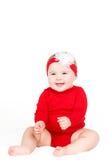 Ståenden av ett lyckligt förtjusande begynnande barn behandla som ett barn lyckligt le flickalin för rött sammanträde på en vit ba Arkivfoto