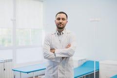 Ståenden av ett lyckligt manligt doktorsanseende med armar korsade på det medicinska kontoret fotografering för bildbyråer