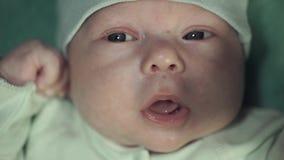 Ståenden av ett nyfött behandla som ett barn pojken i den försiktiga gröna dräkten med en gul fredsmäklare arkivfilmer