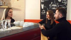 Ståenden av ett par på ett datum i en coffee shop, talar de till uppassaren arkivfilmer