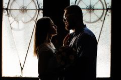 Ståenden av ett romantiskt par i ett panelljus från ett fönster eller gör Arkivfoto