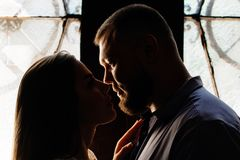 Ståenden av ett romantiskt par i ett panelljus från ett fönster eller gör Arkivbild
