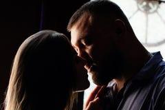 Ståenden av ett romantiskt par i ett panelljus från ett fönster eller gör Royaltyfri Foto
