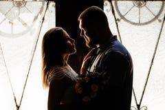 Ståenden av ett romantiskt par i ett panelljus från ett fönster eller gör Royaltyfri Bild