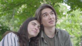 Ståenden av ett ungt le par i tillfällig kläder som spenderar tid i, parkerar tillsammans och att ha ett datum Peka för grabb arkivfilmer
