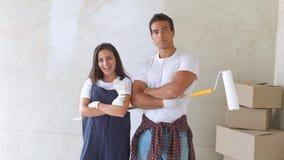 Ståenden av ett ungt par i ett nytt hus är måla och dekorera väggen av deras hus lager videofilmer