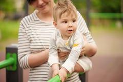 Ståenden av förtjusande behandla som ett barn att le och att spela med hans mamma Arkivfoton