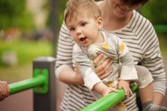 Ståenden av förtjusande behandla som ett barn att le och att spela med hans mamma Royaltyfri Foto