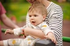 Ståenden av förtjusande behandla som ett barn att le och att spela med hans moder Arkivbild
