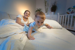 Ståenden av förtjusande behandla som ett barn pojkekrypning på säng på natten Arkivfoto