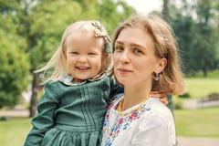 Ståenden av familjmamman med dottern i retro linne för tappning klär med buketten av blommor Arkivfoto