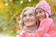 Ståenden av farmodern och sondottern i höst parkerar royaltyfri foto