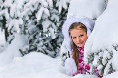 Ståenden av flickan för den lilla ungen i vinter beklär plying i djup snö fotografering för bildbyråer