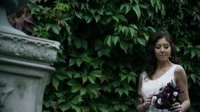 Ståenden av flickan med buketten i hennes händer är le och se in i kamera lager videofilmer