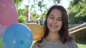 Ståenden av flickan med hänglsenhåll som den färgrika uppblåsbar sväller i panelljus på, parkerar, närbilden som ler på kamera stock video