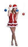 Ståenden av flickan weared i den santa klänningen som leker med, klumpa ihop sig Fotografering för Bildbyråer