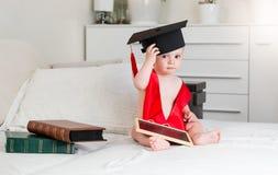Ståenden av 10 gamla månader behandla som ett barn pojken med böcker som bär avläggande av examen Royaltyfri Fotografi