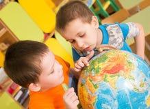 Ståenden av gladlynta le barn i ljus mång--färgad kläder ser och trycker på jordklotshowfingret på översikten i kinderg Arkivbild