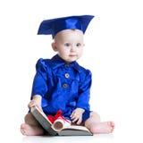 Ståenden av gulligt behandla som ett barn i studenthatt med boken Arkivbilder