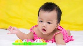 Ståenden av gulligt behandla som ett barn le flickan på sängen med leksaken Royaltyfria Bilder