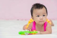 Ståenden av gulligt behandla som ett barn le flickan på sängen med leksaken Arkivfoton