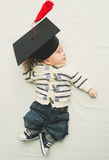 Ståenden av gulligt behandla som ett barn pojken som poserar i svart avläggande av examenlock Royaltyfri Fotografi