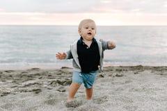 Ståenden av gulligt litet behandla som ett barn pojkebarnet som spelar och undersöker i sanden på stranden under solnedgångytters arkivbild