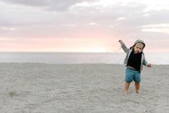 Ståenden av gulligt litet behandla som ett barn pojkebarnet som spelar och undersöker i sanden på stranden under solnedgångytters arkivbilder