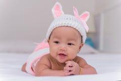 Ståenden av gulligt nyfött behandla som ett barn leende på sängen Arkivbilder