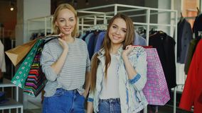 Ståenden av härliga unga kvinnor står med pappers- påsar i deras händer i boutique för kläder för kvinna` s innegrej arkivfilmer