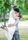 Ståenden av härligt barn kopplar ihop den kvinnliga bruden, och manbrudgummen som kysser i sommar, parkerar Lyftt kvinnafru för m arkivbilder