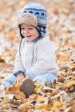 Ståenden av härligt behandla som ett barn pojken som sitter på sidorna säsong för bana för höstfallskog arkivbilder