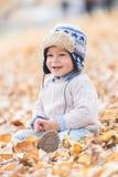 Ståenden av härligt behandla som ett barn pojken som sitter på sidorna säsong för bana för höstfallskog arkivfoton