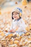Ståenden av härligt behandla som ett barn pojken som sitter på sidorna säsong för bana för höstfallskog royaltyfria foton