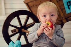 Ståenden av härligt behandla som ett barn pojken som äter äpplet Arkivfoton