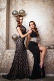 Ståenden av härligt kopplar samman unga kvinnor i ursnygga aftonklänningar Arkivbild