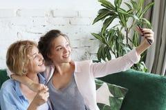 Ståenden av härligt mognar modern och hennes dotter som gör en selfie genom att använda den smarta telefonen och le, hem- och lyc royaltyfria foton