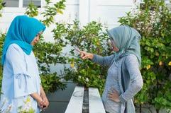 St?enden av ilskna tv? hijabkvinnor har mots?ttningar med grannar arkivbild