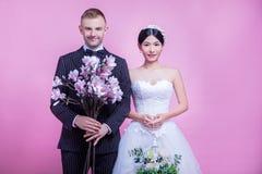 Ståenden av innehavet för mång--person som tillhör en etnisk minoritet brölloppar blommar, medan stå mot rosa bakgrund Royaltyfri Fotografi